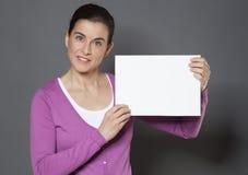 Donna che tiene cartone o carta in bianco per un annuncio Fotografie Stock
