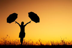 Donna che tiene due ombrelli e siluette di tramonto fotografie stock