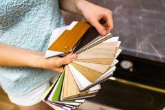 Donna che tiene e che mostra il modello variopinto di struttura e la tavolozza di colore - campioni da scegliere da fotografia stock libera da diritti