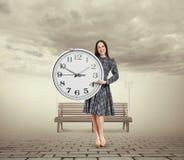 Donna che tiene grande orologio ed indicare Immagine Stock Libera da Diritti
