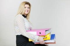 Donna che tiene i raccoglitori variopinti pesanti con i documenti Fotografia Stock