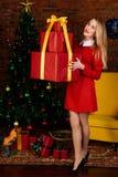 Donna che tiene il grande regalo rosso di Natale Immagine Stock