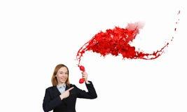 Donna che tiene il microtelefono rosso del telefono immagine stock libera da diritti