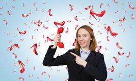 Donna che tiene il microtelefono rosso del telefono fotografie stock