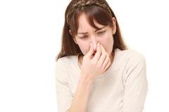 Donna che tiene il suo naso a causa di cattivo odore fotografia stock