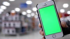 Donna che tiene il telefono cellulare verde dello schermo su bello fondo d'accensione vago video d archivio