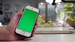 Donna che tiene iphone verde dello schermo con sala da pranzo confusa stock footage