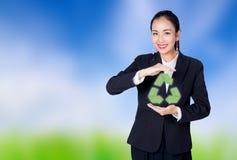 Donna che tiene l'icona di riciclaggio, simbolo per il riciclaggio sulla natura b Fotografie Stock