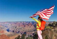 Donna che tiene la bandiera degli Stati Uniti, parco nazionale di Grand Canyon Immagine Stock