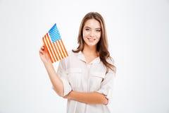 Donna che tiene la bandiera di U.S.A. e che esamina macchina fotografica Fotografia Stock