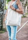 Donna che tiene la borsa vuota della tela Derisione del modello su fotografie stock