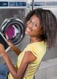 Donna che tiene la compressa di Digital che si siede alla lavanderia automatica Fotografie Stock Libere da Diritti