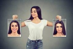 Donna che tiene le immagini con le buone e cattive emozioni che hanno oscillazioni di umore e che sorridono al positivo fotografie stock libere da diritti