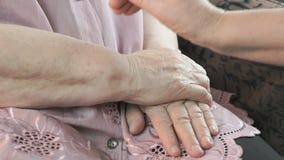 Donna che tiene le mani corrugate floscie della donna anziana stock footage
