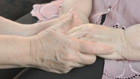 Donna che tiene le mani corrugate floscie della donna invecchiata archivi video