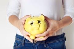 Donna che tiene maiale giallo Immagine Stock