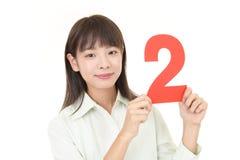 Donna che tiene numero due fotografia stock libera da diritti