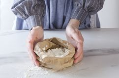 Donna che tiene sacco di carta con farina bianca Tavolo da cucina e cuoco unico accanto, chi che si prepara per cuocere fotografia stock