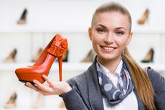 Donna che tiene scarpa di cuoio arancio Fotografie Stock Libere da Diritti