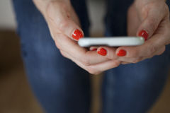 Donna che tiene Smartphone con Coral Nails fotografia stock libera da diritti
