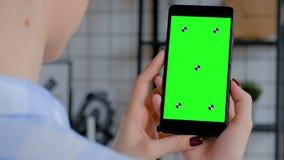 Donna che tiene smartphone nero con lo schermo verde in bianco - concetto chiave di intensità stock footage