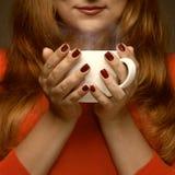 Donna che tiene tazza calda ed i sorrisi Fotografia Stock