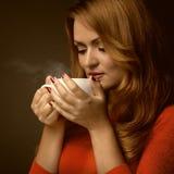 Donna che tiene tazza calda ed i sorrisi Fotografia Stock Libera da Diritti