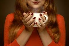 Donna che tiene tazza calda ed i sorrisi Fotografie Stock Libere da Diritti