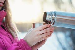 Donna che tiene tazza dal termos in mani ai rami nevosi del fondo degli alberi di inverno Fotografie Stock