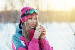Donna che tiene tazza dal termos in mani ai rami nevosi del fondo degli alberi di inverno Fotografie Stock Libere da Diritti