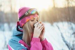 Donna che tiene tazza dal termos in mani ed il tè della bevanda ai rami nevosi del fondo degli alberi di inverno Fotografia Stock