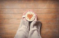 Donna che tiene tazza di caffè calda, con forma del cuore fotografia stock