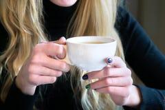 Donna che tiene tazza di tè in un caffè Immagini Stock Libere da Diritti