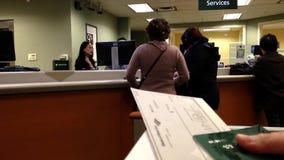 Donna che tiene un assegno dentro la banca del TD archivi video