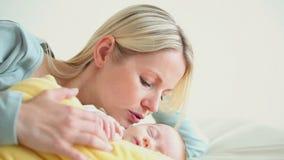 Donna che tiene un bambino in una coperta gialla archivi video