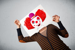 Donna che tiene un cartone con un pagliaccio su davanti al suo hea Fotografia Stock Libera da Diritti