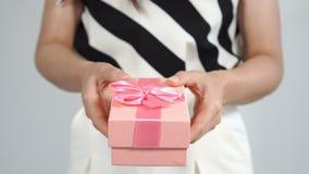 Donna che tiene un contenitore di regalo in un gesto di dare archivi video