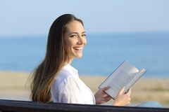 Donna che tiene un libro aperto che esamina macchina fotografica Immagini Stock Libere da Diritti