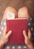 Donna che tiene un libro rosso con un messaggio di carta Fotografia Stock Libera da Diritti