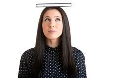 Donna che tiene un libro sopra la sua testa Fotografia Stock