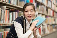Donna che tiene un libro vicino allo scaffale per libri Fotografie Stock Libere da Diritti