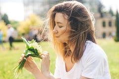 Donna che tiene un mazzo di lilly dei fiori della valle fotografia stock