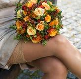 Donna che tiene un mazzo di rose arancio in sue mani che indossano tenuta Immagini Stock