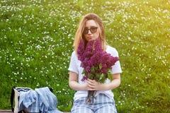 Donna che tiene un mazzo vivo di fiori lilla contro il fondo floreale verde di estate immagine stock libera da diritti