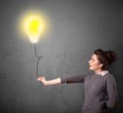 Donna che tiene un pallone della lampadina Fotografia Stock