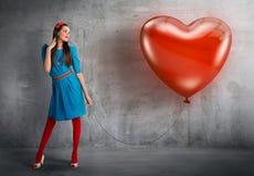 Donna che tiene un pallone a forma di del cuore Fotografie Stock Libere da Diritti