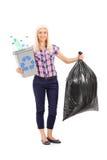 Donna che tiene un recipiente di riciclaggio e una borsa di rifiuti Immagini Stock