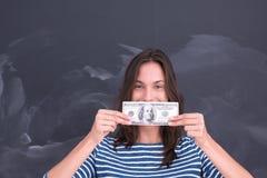 Donna che tiene una banconota davanti al tavolo da disegno del gesso Immagine Stock Libera da Diritti