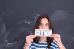 Donna che tiene una banconota davanti al tavolo da disegno del gesso Immagini Stock Libere da Diritti