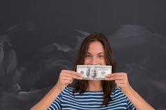 Donna che tiene una banconota davanti al tavolo da disegno del gesso Immagini Stock